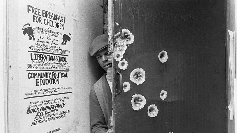 An unidentified member of the Black Panthers peeks around a bullet-pocked door which police blasted with gunfire during a predawn raid. A poster shows some of the Panthers' social programs. Bettmann/Getty Images