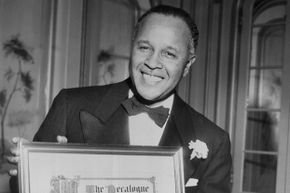 Pioneering chemist Percy Julian holds an award from the Decalogue Society of Lawyers, ca. 1950s.