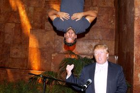 "Magician David Blaine hangs above developer Donald Trump during a press conference promoting ""David Blaine: Dive of Death."""