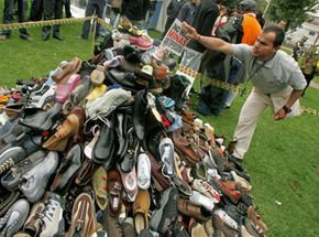 """Edgar Moreno, victim of a landmine blast, places a flag bearing the words """"No more anti-personnel mines"""" on a heap of shoes in Bogota, Colombia."""