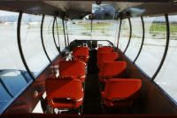Forward view inside of gondola, showing pilot seats/controls (front) and passenger seats