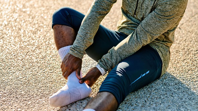 runner looking at foot in socks