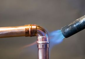 Hot blowtorch soldering right-angle elbow to 15-mm copper tube