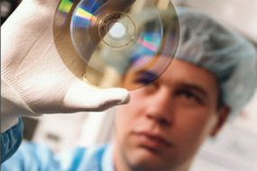 A BD-ROM disc researcher holds a disc up to the light.