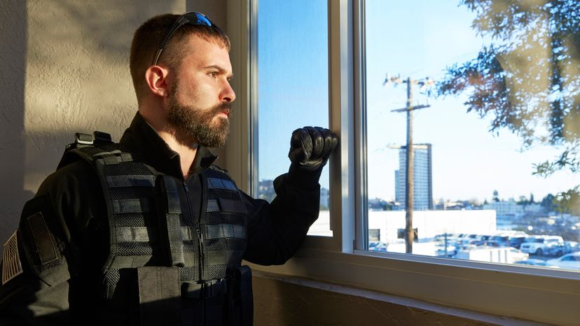 Man in body armor and bulletproof vest gazing out the window
