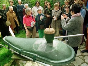 """A designer displays her environmentally friendly """"Ecopod"""" coffin along with a papier mâché acorn urn for cremains."""