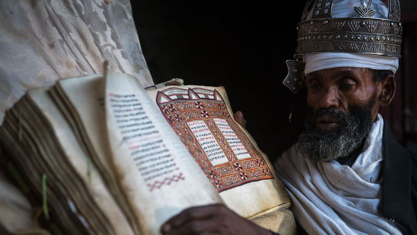 Ethiopian Orthodox priest shows an ancient Bible