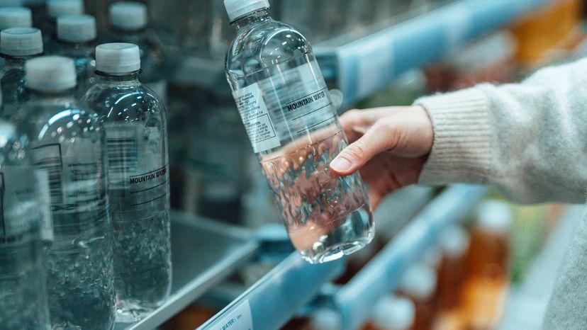 Woman Pulling Bottled Water from Supermarket Shelf
