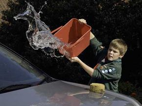 A Boy Scout washes a car.