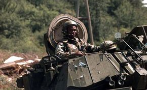 A U.S. Army M2A2 Bradley crew member stands up through the open turret hatch.