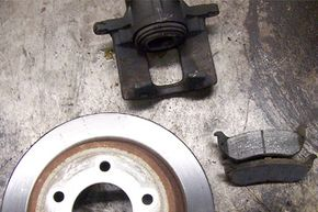 This photo shows a typical disc brake assembly with rotor, pads and caliper. This assembly was replaced after the caliper froze and the pads wore down to almost no thickness. Heat warped the rotor and prevented the brakes from working effectively.