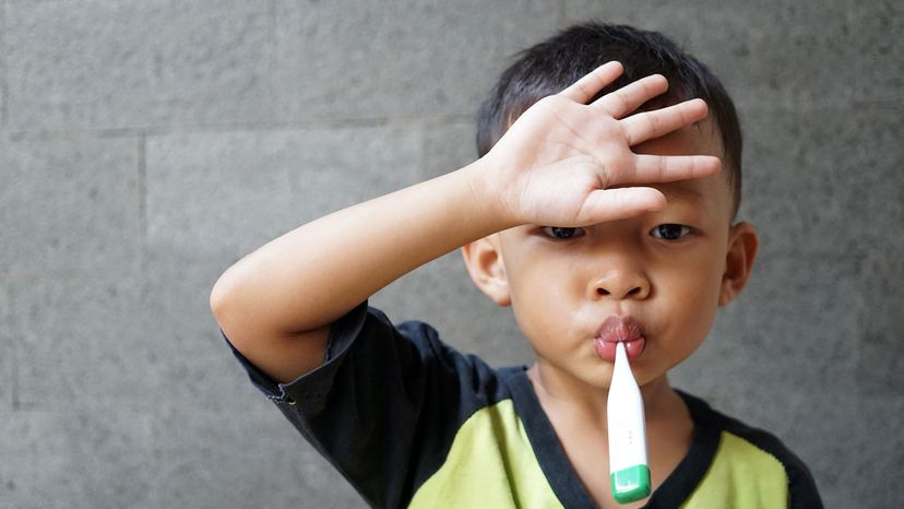 Asian kid holding forehead