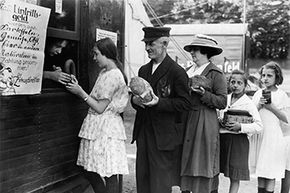 After World War I, the collapse of German currency led to material assets being used for money. Here, people are exchanging bread, jam and other goods for circus tickets. The phrase really refers to people being pacified by their government with food and entertainment.