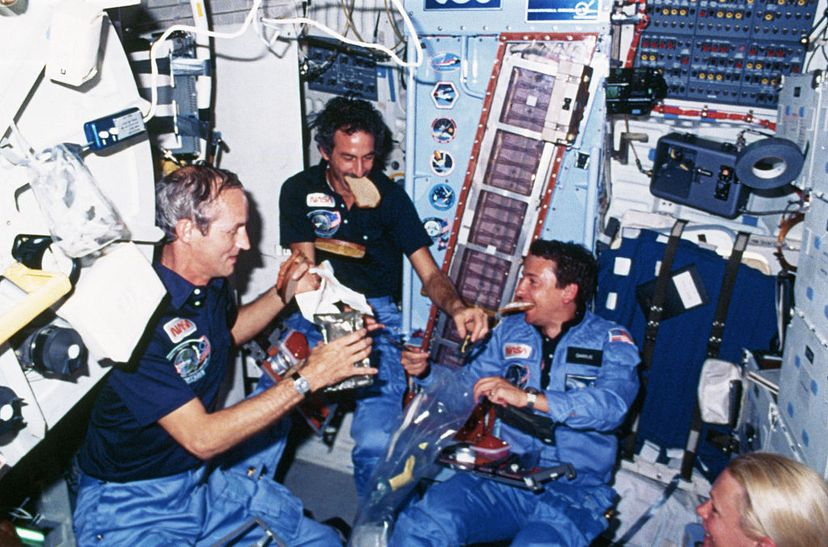 Two astronauts eat bread on board the Space Shuttle Discovery.  CORBIS/Corbis via Getty Images