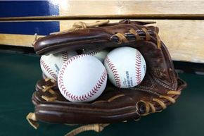 A detailed view of a baseball glove and balls on the bench prior to the start of a game between the Pittsburgh Pirates and the Detroit Tigers at Comerica Park, Detroit.