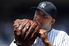 Pitcher CC Sabathia of the New York Yankees tightens his glove strings in an MLB baseball game against the Tampa Bay Rays. Players have lots of techniques for breaking in gloves. See more baseball pictures.