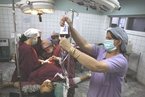 Doctors perform a C-section in Kabul, Afghanistan, in October 2007. One out of nine Afghan women die during pregnancy or soon after.