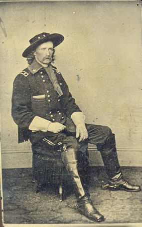 """George A. Custer in Military Dress Wearing Hat and Gloves Seated on an Ottoman,"""" circa 1864."""