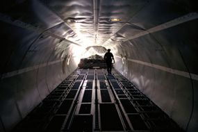 A U.S. Customs inspector examines the cargo load in an airplane arriving from overseas.