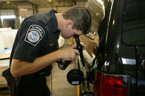 This CBP officer uses a high-tech device to peek inside this van for contraband.