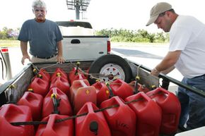 Reynolds Tanner (left) and his son, Ryan, fill more than 20 gas cans at a gas station in Sebring, Fla.