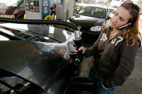 A customer pumps gas into her car at a gas station in San Jose, Calif.