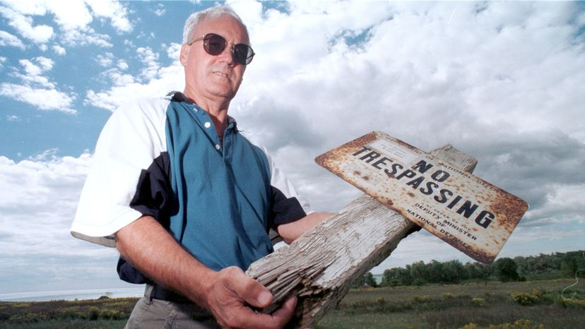 """Lynn Philip Hodgson, author of the book """"Inside – Camp X,"""" holds an old sign from Camp X on the grounds of the former spy training school. Paul Irish/Toronto Star via Getty Images"""