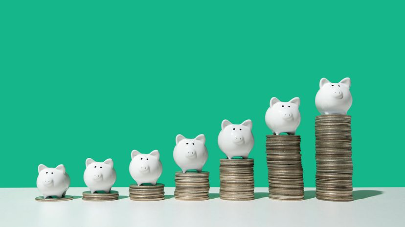 stacks of coins under piggy banks