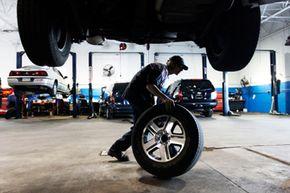 A mechanic rolls a tire