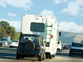 Towing a car behind an SUV can be done easily with a self-aligning car-mounted tow bar.