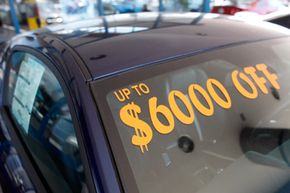 The discount available is written on the windshield of an unsold vehicle at a Ford dealership in east Denver.