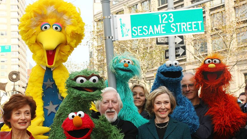 Puppeteer Caroll Spinney, Sesame Street co-founder and TV producer Joan Ganz Cooney, and Sesame Street cast members pose under a '123 Sesame Street' sign