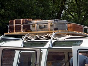 This VW van has an aftermarket roof rack installed. The luggage looks strapped down. Good. Wait! Don't forget the luggage cover.