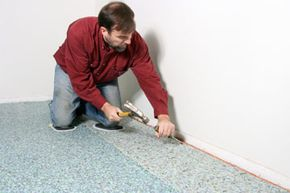 A carpet installer lays down the underpad before moving on to the carpet.