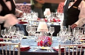 The catering staff carefully checks each place setting -- making sure the glasses gleam and the silver shines!