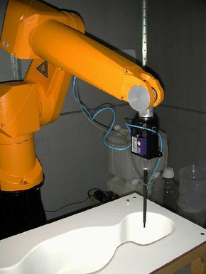 A probe attached to a mechanical arm is directed to take SAR measurements throughout a human-shaped mold. The mold is filled with a liquid mixture that simulates the electrical properties of human tissue.