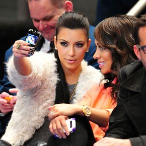 Queen of the selfie, Kim Kardashian, takes a picture with her smartphone of herself and friend La La Anthony at a New York Knicks game.
