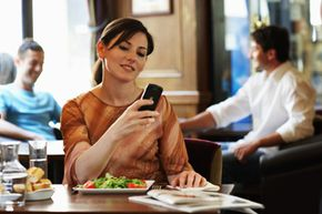 A woman checks messages on her mobile phone. Cell phones have truly taken over the world. See cell phone pictures.