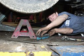 Curtis Blackburn, a blind mechanic at Moonlight Automotive in Greenwood, Ind., switches sockets while working on a truck's transmission on March 24, 2004. His lack of vision doesn't hinder his ability to diagnose and fix car problems.