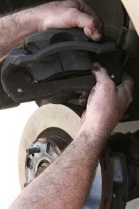 Once the brake caliper piston has been retracted, you can slip the new pads into the slots where you found the old ones.