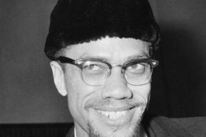 Malcolm X arrives at London Airport in 1965. He had just flown back from France after being refused admittance to that country on the grounds that his presence might incite disturbances.