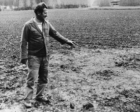 a man points to a spot in a field