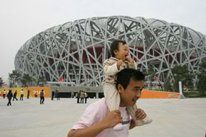 """Beijing Image Gallery A man poses with his baby outside of the National Stadium or """"Bird's Nest"""" in Beijing. China has experienced a surge in Olympic-themed baby names. See more pictures of Beijing."""