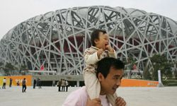 """A man poses with his baby outside of the National Stadium or """"Bird's Nest"""" in Beijing. China has experienced a surge in Olympic-themed baby names."""