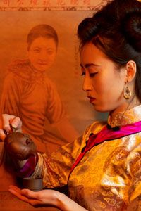 A woman wearing a traditional Chinese dress pours tea.