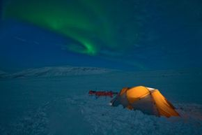 A snowy campsite with a lovely view of the aurora borealis. Yes, please!