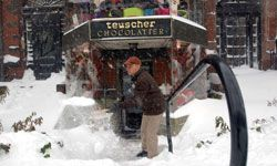 A Boston man shovels the Teuscher Chocolate shop out of the snow.