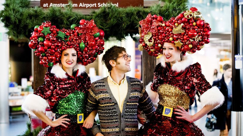 Two women in Christmas costumes pose with a tourist.