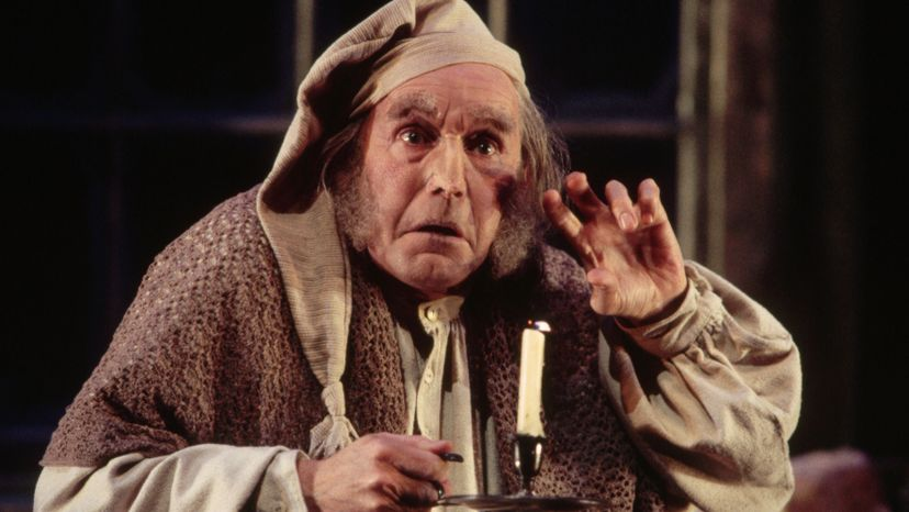 Ebenezer Scrooge holds a candle stick.