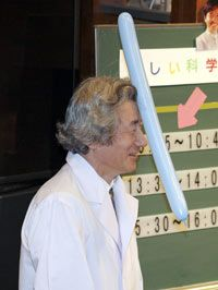 Japanese Prime Minister Junichiro Koizumi laughs as a balloon clings to him with a static electrical charge. 